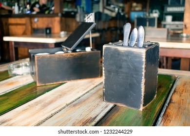 Flatware, cutlery, silverware in wooden box and Paper napkins, pepper and salt shaker on the table. Restaurant interior, pub, cafe background