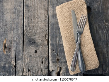Flatware on a rustic wooden table with space for text