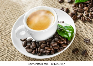 Flavor of coffee. Espresso in a white cup with stream on a canvas texture background. Macro, close-up, top view, copy space. Coffee beans and green leaves. Aroma. Hot