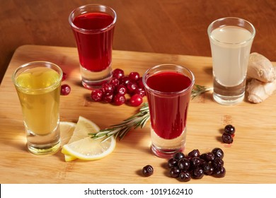 Flavored fruit spiced liqueurs on wooden board. Citrus, berries, ginger