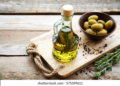 Flavored olive oil with rosemary and pepper on wooden background