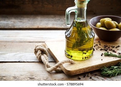Flavored olive oil with rosemary and pepper on wooden background. Copy space.