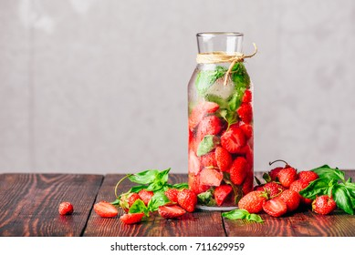 Flavored Water in Bottle with Fresh Strawberry and Basil Leaves. Scattered Ingredients on Wooden Table. Copy Space.