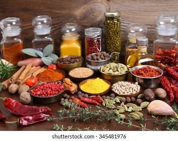 Flavorful, colorful spices in metal  bowls and glass bottles on dark wooden background.
