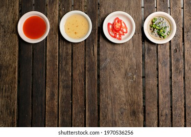 Flavoring food on wooden background at restaurant.