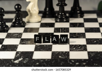 Flaw the word or concept represented by black and white letter tiles on a marble chessboard with chess pieces