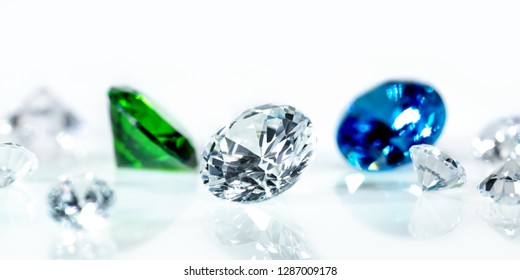 Flawless diamonds, blue sapphire and a green emerald in front of white background, banner