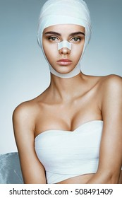 Flawless face of young beautiful woman. Photo of girl wrapped in medical bandages. Plastic Surgery concept