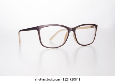 Flawless stylish brown optical glasses on a white neutral background with shadows under object.