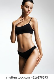 Flawless woman in black bikini on grey background. Photo of girl with slim toned body. Beauty and body care concept