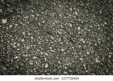 Flaws and defects give to weakness shown by cracked pavement.  Imperfections and rough asphalt.