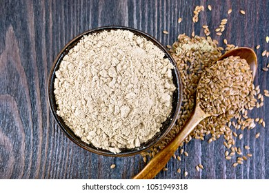 Flax flour in a bowl, seeds in a spoon and on a table on the background of a wooden board on top
