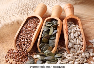 Flax, pumpkin and sunflower seeds in wooden spoons