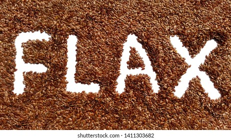 Flax seed heap with word flax of seed isolated. Flaxseed pile background. Closeup macro organic flax seed crop.Top view flaxseed heap, flat lay. Healthy brown seed food. Raw flaxseed for linseed oil