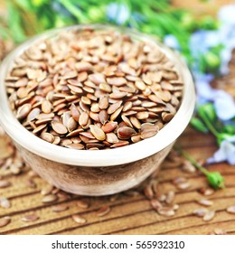 Flax seeds in bowl on linum plants and linseeds background, selective focus, shallow DOF