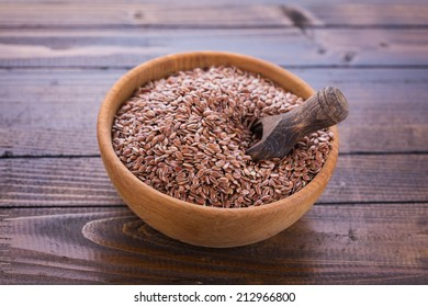 Flax seeds in bowl on wooden background. Selective focus, horizontal.