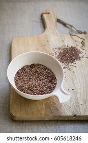 Flax seeds in bowl on wooden desk on linen cloth background