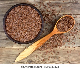 Flax seeds in bowl with scattered grains on wooden background with wooden spoon. Also known as Linseed, Flaxseed and Common Flax. Pile of grains, isolated white background.