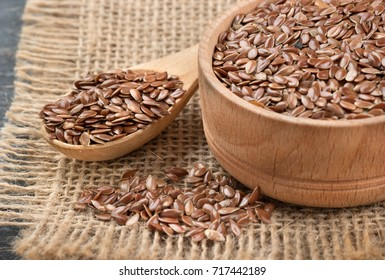 Flax seeds in a bowl and spoon with scattered beans on sackcloth closeup