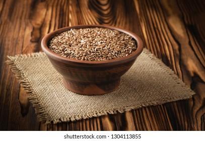 Flax seeds in a clay bowl and on linen fabric.