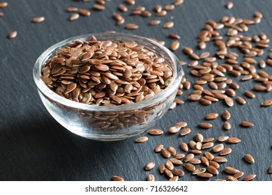 Flax seeds in a glass bowl on a dark background