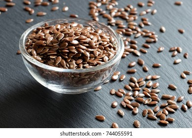 Flax seeds in a glass bowl on a gray background