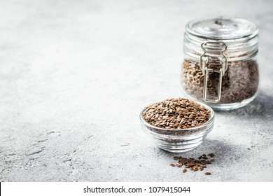 Flax seeds in glass jar and bowl on concrete background. Selective focus, space for text.