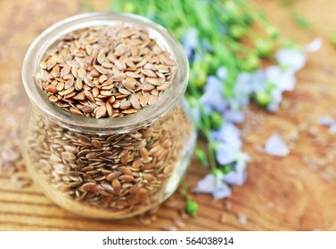 Flax seeds in glass jar on blue linum plants background, selective focus, shallow DOF