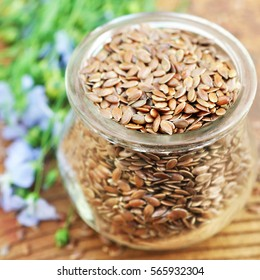 Flax seeds in glass jar on linum plants and linseeds background, selective focus, shallow DOF