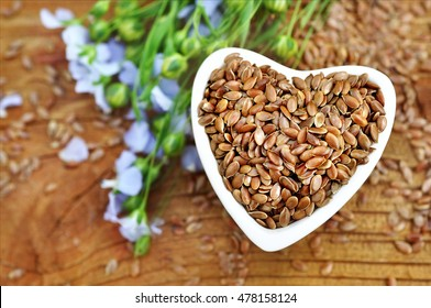 Flax seeds in heart-shaped bowl and linum plants, wooden background selective focus, shallow DOF