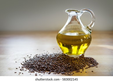 flax seeds and linseed oil in a glass jug on a wooden kitchen board, healthy diet with omega 3 fatty acids, selected focus, narrow depth of field