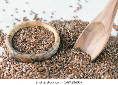 Flax seeds Linum usitatissimum - a useful and medicinal product. Close-up. Spoon and plate of natural olive tree among flax seeds. Product for beauty and health. Proper nutrition.