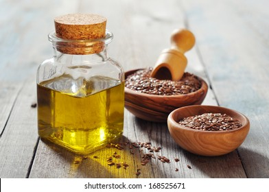 Flax seeds and oil in bottle on wooden background