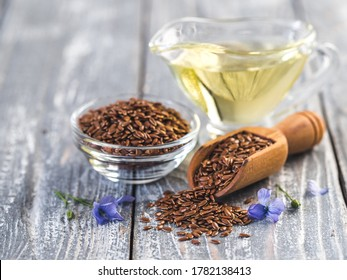 Flax seeds and flax oil. Brown linen seeds, flaxseed oil and blue flax flowers on old gray wooden background. Copy space