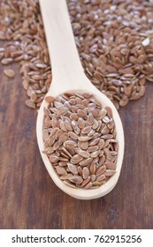 Flax seeds on the wooden background - Linum usitatissimum