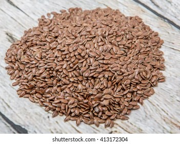 Flax seeds over wooden background