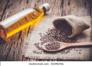 Flax seeds in the sack and oli on wooden background, vintage color tone