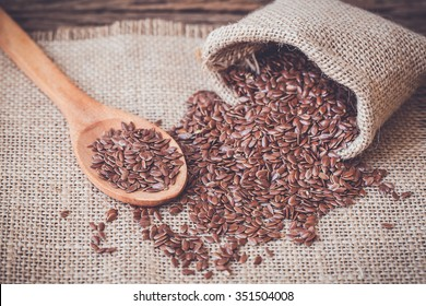 Flax seeds in the sack on wooden background, vintage color tone