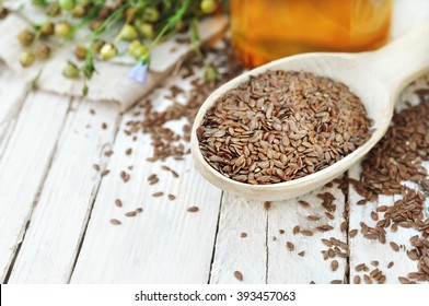 Flax seeds in spoon with linseed oil and linum plants, white wooden background