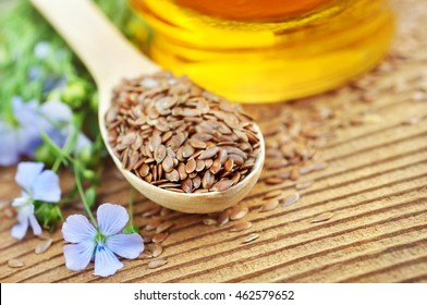 Flax seeds in spoon with linseed oil and linum plants, wooden background