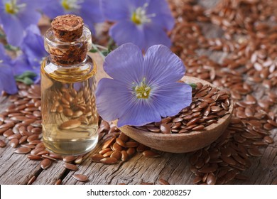 flax seeds in a spoon and oil in a bottle on the table close-up horizontal