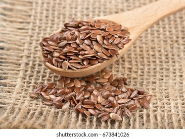 Flax seeds in the spoon and scattered beans on sackcloth