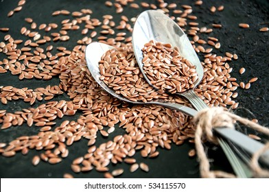 Flax seeds in spoons over dark background.