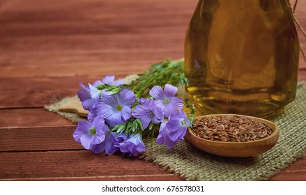 Flax seeds in vintage spoon,  linum plants with flower and linseed oil on glass bottle  with vintage sackcloth on wooden background.  Conceptual photo for medicine and dietary nutrition.