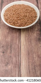 Flax seeds in white bowl over wooden background