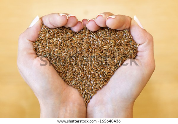 Flax seeds in woman's hands shaping heart