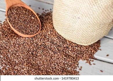 Flax seeds in a wood spoon on a wooden background. Linseed is scattered from a linen bag.