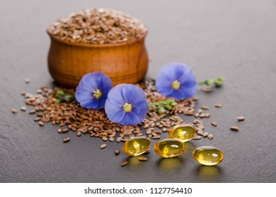 Flax seeds in the wooden bowl, beauty flower and oil in caps on a grey background. Phytotherapy.