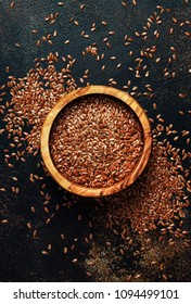 Flax seeds in a wooden bowl, brown background, top view