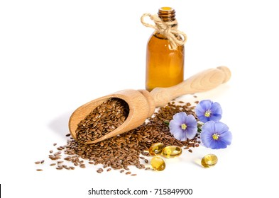 Flax seeds in the wooden scoop, bottle with oil and  beauty flowers isolated on white background.
